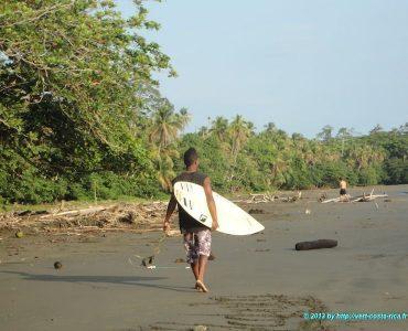 Surfeur sur la plage de sable noir du village de Cahuita au Costa Rica